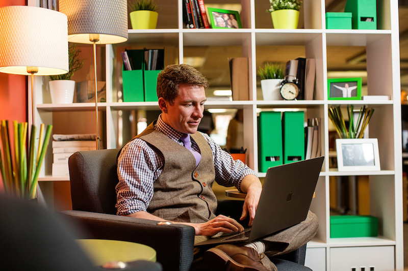 Employee working on laptop in area with bookshelf and cozy chairs