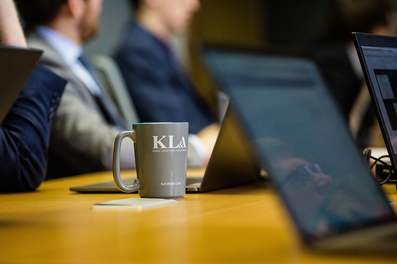 Meeting in conference rooms with laptops and KLA mug