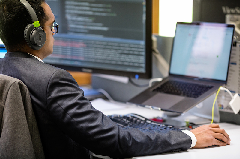 Employee wearing headphones working on custom software